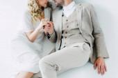 oříznutý pohled na nevěstu ve svatebních šatech a ženich držení rukou