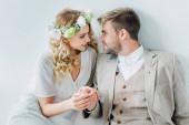 Fotografia sposa attraente e bello sposo tenendosi per mano e guardando lun laltro