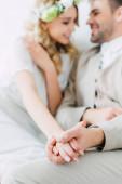 selektivní zaostření nevěsty na svatebních šatech a ženich držení rukou