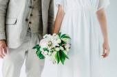 oříznutý pohled na nevěstu s kyticí a ženichem v obleku