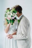 menyasszony a menyasszonyi ruha és a vőlegény ölelgetés és gazdaság csokor