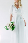 cropped view of bride in wedding dress holding bouquet isolated on white