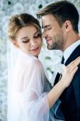 vonzó menyasszony és a szép vőlegény átölelve a csukott szemmel
