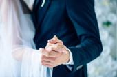 Fényképek nyírt kilátás menyasszony esküvői ruha és vőlegény kezében