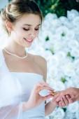 Fotografia sposa attraente e sorridente mettendo anello di nozze sul dito