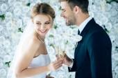přitažlivá nevěsta a pohledný ženich s úsměvem a cinčení sklenicemi šampaňského