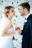 Fényképek vonzó menyasszony és a szép vőlegény mosolygó és csengő pezsgővel szemüveg