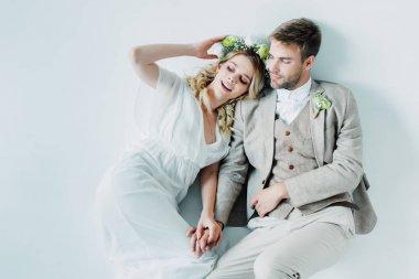 attractive bride and handsome bridegroom hugging and looking away