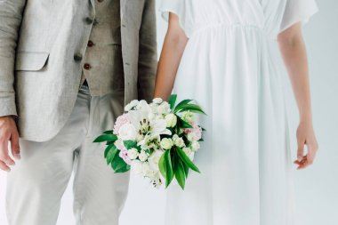 cropped view of bride with bouquet and bridegroom in suit