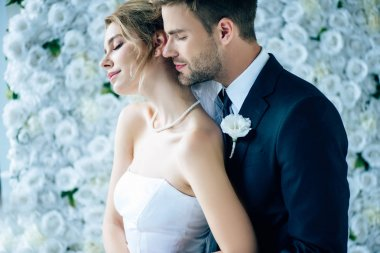 attractive bride and handsome bridegroom hugging with closed eyes
