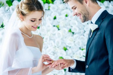 attractive and smiling bride putting wedding ring on finger