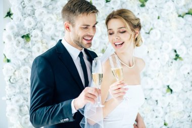 Attractive bride and handsome bridegroom smiling and clinking with champagne glasses stock vector