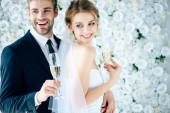 atraktivní nevěsta a pohledný ženich s úsměvem a přidržením skleniček šampaňského