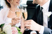 Fotografie cropped view of bride and bridegroom clinking with champagne glasses