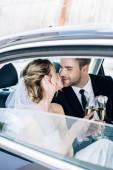 Fényképek vonzó menyasszony és a csinos vőlegény csók és csengő pezsgővel szemüveg