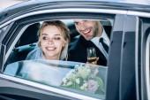 attraktive Braut und schöner Bräutigam klirren mit Champagnergläsern