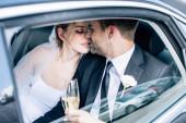 Fotografie attraktive Braut und stattliche Bräutigam küssen und halten Champagner Gläser