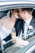 attraktive Braut und stattliche Bräutigam küssen und halten Champagner Glas
