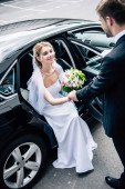 vőlegény öltöny ad kezet a vonzó és mosolygó menyasszony csokor