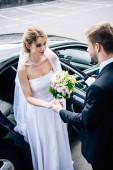 Fényképek vőlegény öltöny ad kezet a vonzó és mosolygó menyasszony csokor