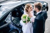 Fotografia sposa in abito baciare attraente e bionda sposa con bouquet