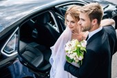 handsome bridegroom in suit hugging attractive and blonde bride with bouquet