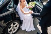 abgeschnittene Ansicht des Bräutigams im Anzug, der der Braut mit Blumenstrauß die Hand reicht