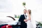 pohledný ženich v obleku, který si objímat atraktivní a blonďatou nevěstu s kyticí
