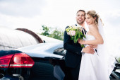 Photo handsome bridegroom in suit hugging attractive and blonde bride with bouquet