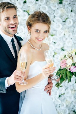 Attractive bride and handsome bridegroom smiling and holding champagne glasses stock vector