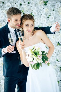 Attractive bride and handsome bridegroom smiling and taking selfie stock vector