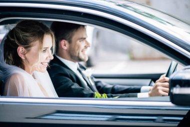 selective focus of attractive bride in bridal veil and bridegroom smiling in car