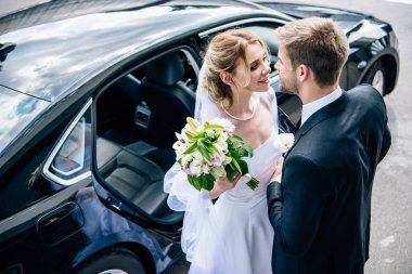 bridegroom in suit kissing attractive and blonde bride with bouquet