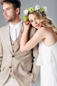 menyasszony esküvői ruha és koszorú ölelgetés szép vőlegény a ruha izolált szürke