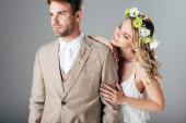 Fényképek menyasszony esküvői ruha és koszorú ölelgetés szép vőlegény a ruha izolált szürke
