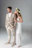 nevěsta ve svatebních šatech a věnec s hezkou ženichem v obleku