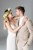 handsome bridegroom in suit hugging with bride in wedding dress and wreath isolated on grey