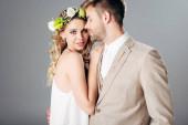 Fényképek szép vőlegény öltönyt átölelve a menyasszony a menyasszonyi ruha és koszorú izolált szürke