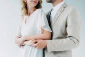 nyírt kilátás vőlegény öltöny átölelve menyasszony esküvői ruha izolált fehér