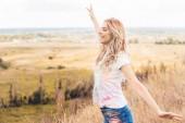 Fotografie attraktive Frau im T-Shirt mit ausgestreckten Händen lächelnd und wegschauend