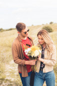 Fotografie handsome man in glasses giving bouquet to blonde woman