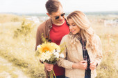 handsome man in glasses giving bouquet to blonde woman