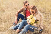 Fotografie attractive woman with bouquet and handsome man smiling and sitting outside