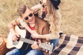 pohledný muž hrající na akustickou kytaru a atraktivní ženu, která ho objala