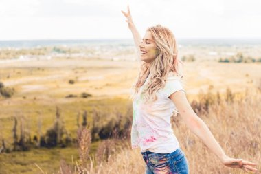 attractive woman in t-shirt with outstretched hands smiling and looking away