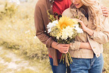 cropped view of man in shirt giving bouquet to blonde woman
