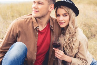 Handsome man looking away and attractive woman in hat holding wine glass stock vector