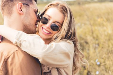 Attractive woman hugging and kissing with handsome man in sunglasses stock vector
