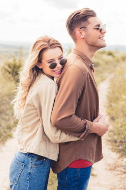 Attractive and smiling woman hugging handsome man in sunglasses stock vector