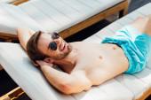 šťastný člověk v slunečních brýlích na lenošáku v letovisku